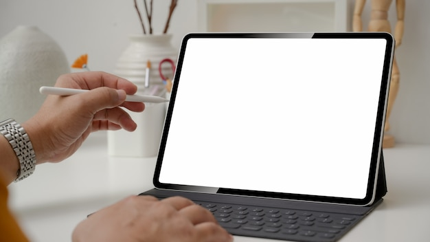 Cropped shot of designer using digital tablet with stylus pen on white table
