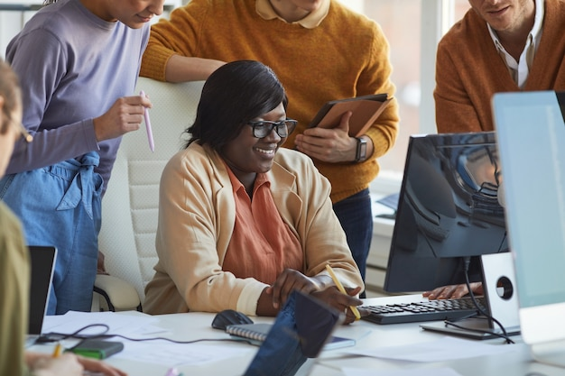 Cropped shot of diverse it development team collaborating on project with smiling african-american woman using computer in software production studio