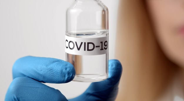 Cropped shot of doctor's fingers in gloves holding vaccine vial with covid-19 inscription, selective