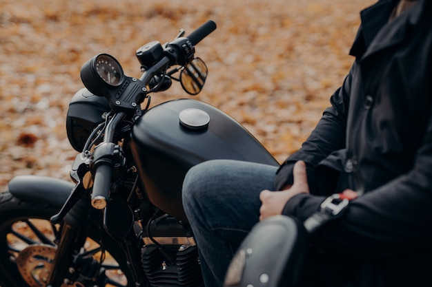 Cropped shot of faceless biker poses on fast motorbike, stops in park, ground covered with fallen leaves
