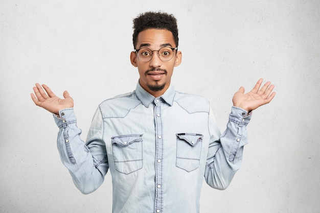 Cropped shot of fashionable young male wears denim clothes and glasses, gestures with hands,