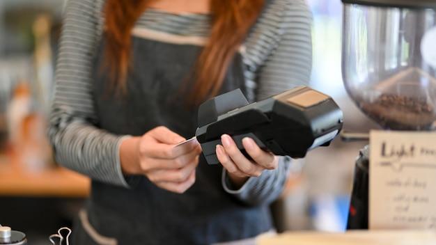 자른 샷 결제 단말기에서 신용카드를 꺼내는 여성 바리스타 비접촉식 결제