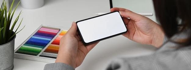 Cropped shot of female designer looking for information on mock-up smartphone