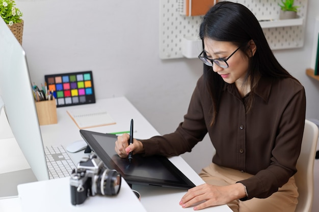 Cropped shot of female designer working with drawing tablet on computer desk in office room