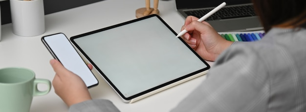 Cropped shot of female designer working with mock-up tablet while looking for information on smartphone