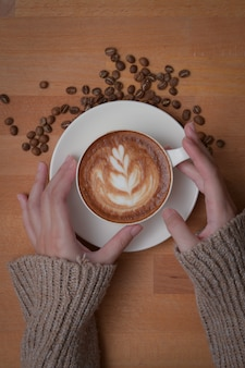 Cropped shot of female hands holding a cup of latte coffee on wooden worktable decorated with coffee beans