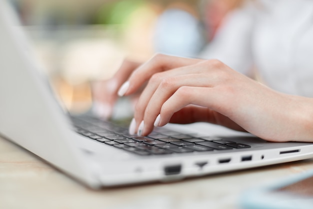 Cropped shot of female hands with nice manicure keyboards on laptop computer, works from home, sits at table and searches internet