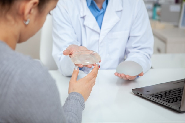 Cropped shot of a female patient examining silicone breast implants, during medical appointment with her plastic surgeon