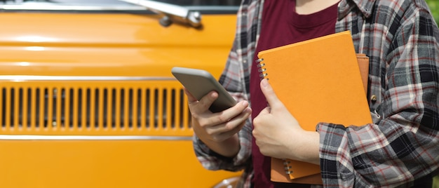 Cropped shot of female worker holding notebooks and using smartphone while standing in front of her car