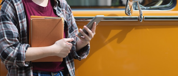 Cropped shot of female worker holding notebooks and using smartphone while standing in front of her van