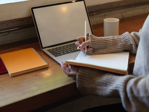 Cropped shot female writing no blank notebook while siting at wooden worktable with mock up laptop