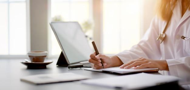 Обрезанный снимок молодой женщины-врача, работающей с медицинскими картами и результатами экзаменов с планшетом