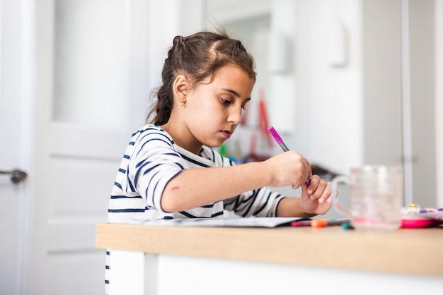Cropped shot of a focused little girl making a picture using different types of art supplies while being seated at a table inside during the day