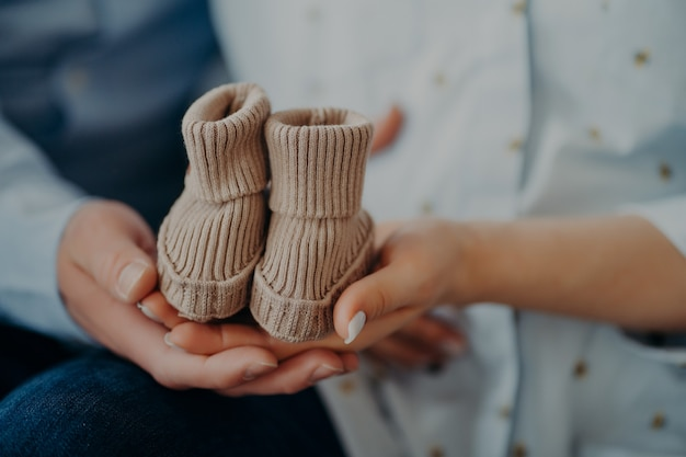 Cropped shot of future parents anticipate for child hold baby boots show small shoes for coming baby. parenthood pregnancy birth love and family concept.