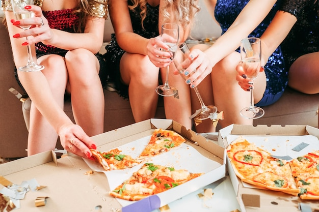 Cropped shot of girls in sparkling mini dresses hanging out, sitting, eating pizza from boxes, drinking champagne.