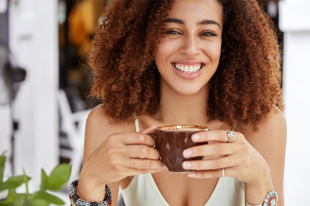 Cropped shot of good looking cheerful african american female holds cup of coffee, has lunch in cozy cafeteria, rests after excursion, recreats in resort country