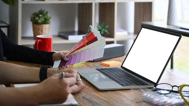 オフィスでラップトップコンピューターを操作するデザイナーのクロップドショットグループ。