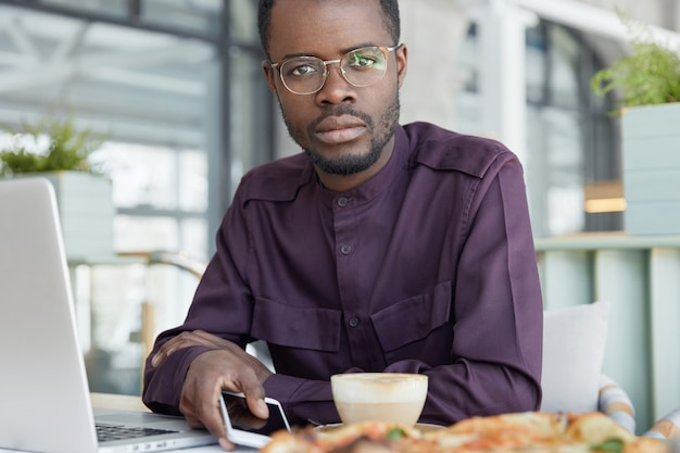 Cropped shot of handsome dark skinned man wears round spectacles and formal shirt, uses modern technologies for work