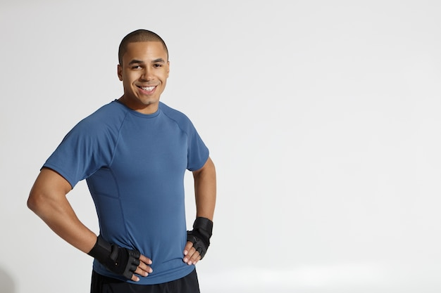 Cropped shot of happy young afro american bodybuilder looking at camera and grinning confidently, keeping hands on his waist, posing against white studio wall background with copy space for your text