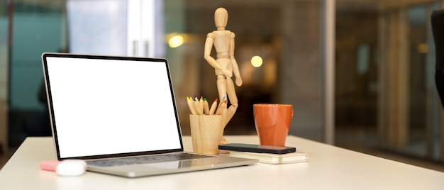 Cropped shot of home office desk with laptop wooden figure coloured pencils and supplies