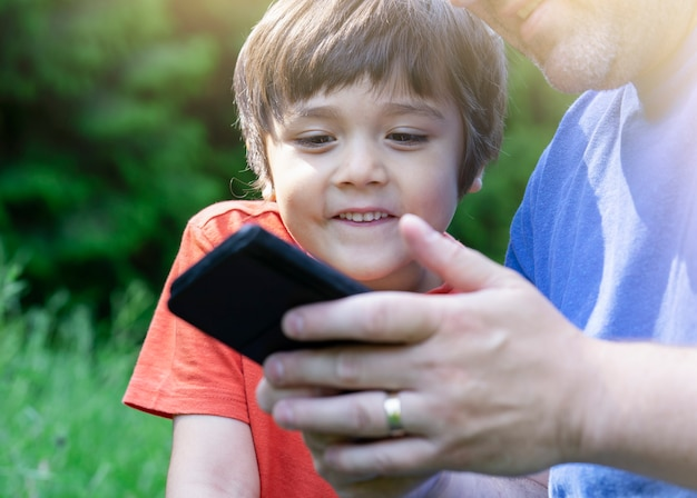 Cropped shot kid boy siting in the park with parent playing game on smart phone,  child looking at mobile phone with blurry green nature