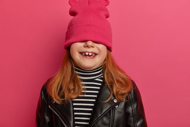 Immagine ritagliata di una graziosa bambina che si nasconde sotto il cappello, si diverte da sola, sorride in modo ampio mostra denti da latte bianchi, sogna di diventare una modella che indossa un'elegante giacca di pelle, sorride dalla felicità