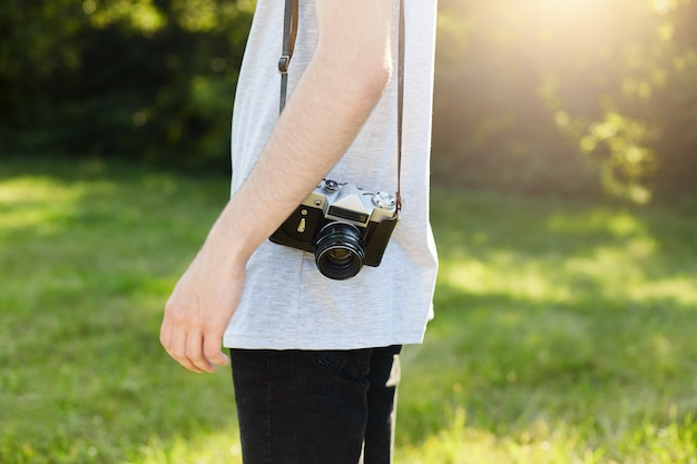 Cropped shot of male`s body with retro camera on shoulder standing at green grass going to photographing someone