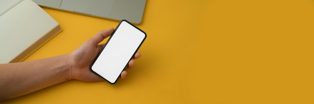 Cropped shot of a man holding blank screen smartphone with supplies