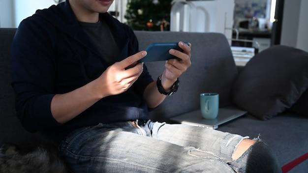 Cropped shot man looking at his smartphone and sitting at sofa.