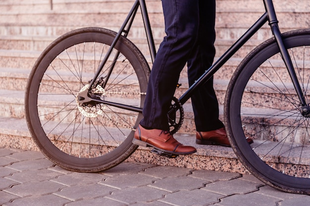 Cropped shot of man riding bicycle on street