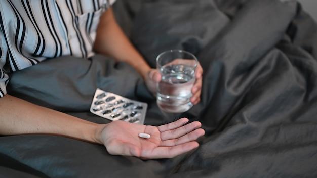 그의 침대에 앉아서 약을 복용 잘린 샷 남자.