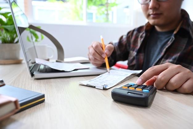 Cropped shot man using computer laptop and calculating domestic bills at home.
