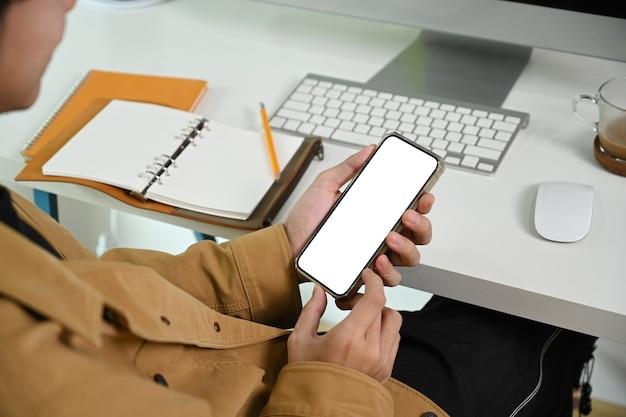 Обрезанный снимок человека с помощью смартфона, сидя на своем рабочем месте.