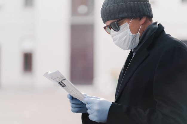 Cropped shot of man wears facial medical mask and protective rubber gloves,