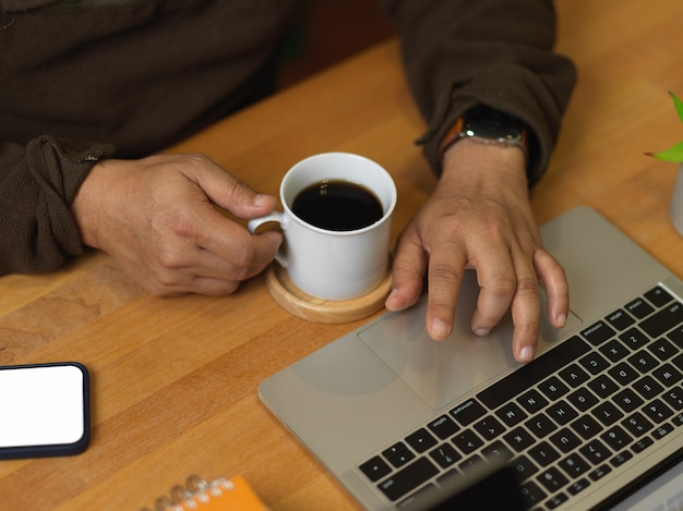 Cropped shot of man working with laptop and holding coffee cup on wooden table with smartphone