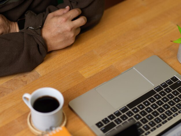 Cropped shot of man working with laptop on wooden table with coffee cup
