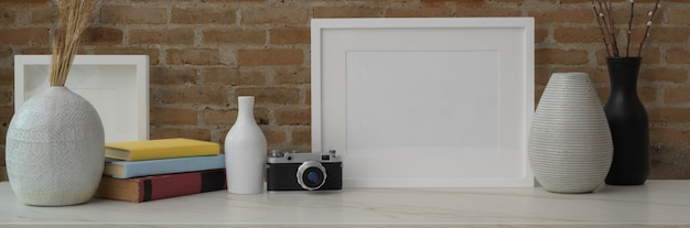 Cropped shot of marble counter decorated with frames, ceramic vases, camera and books