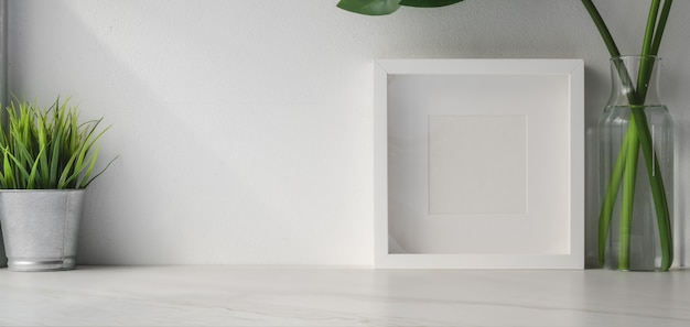 Cropped shot of minimal workspace with mock up frame and tree pot on white wooden table and white wall background