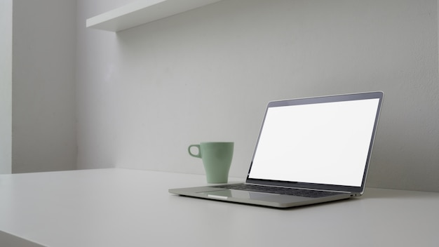 Cropped shot of minimal workspace with open blank screen laptop, mug and copy space