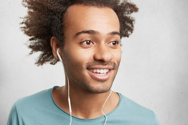 Cropped shot of mixed race unshaven man looks happily as listens to pleasant songs in earphones