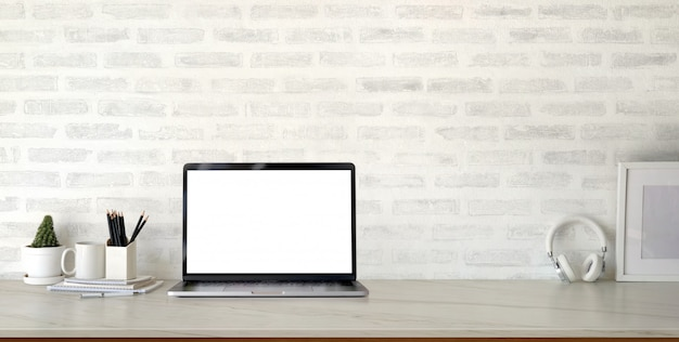 Cropped shot of modern stylish workplace with open blank screen laptop computer and office supplies on marble desk and brick wall