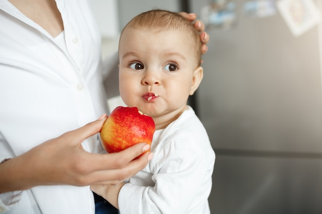 Cropped shot of mother giving baby slice of apple