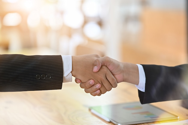 Cropped shot negotiating business handshake with gesturing.