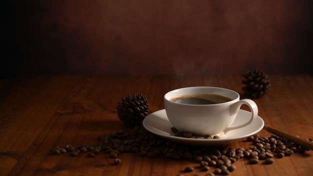 나무 테이블에 장식 된 원두 커피와 뜨거운 커피 한 잔의 자른 샷
