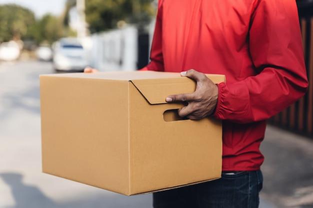 빨간 제복을 입은 배달원의 자른 샷이 거리에 있는 우편 소포 가판대를 들고 고객에게 물건을 배달하기 위해 gps 주소를 확인하는 휴대폰을 바라보고 있습니다. covid-19 전염병 동안 배달 서비스.