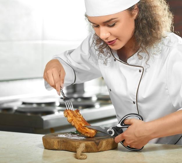 Обрезанный снимок женщины-шеф-повара, готовящей вкусный куриный стейк на гриле на своей кухне, режущая его ножницами, еда в ресторане copyspace, поедающая мясо концепции.