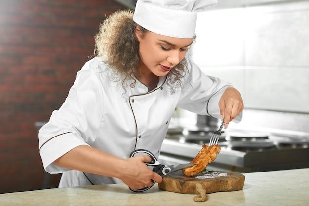 Обрезанный снимок женщины-шеф-повара, которая готовит вкусный куриный стейк на гриле на кухне, режет его ножницами