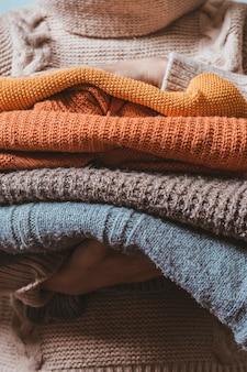 Обрезанный снимок женщины, держащей вязаные теплые свитера, готовящей одежду к наступающему холодному сезону ...