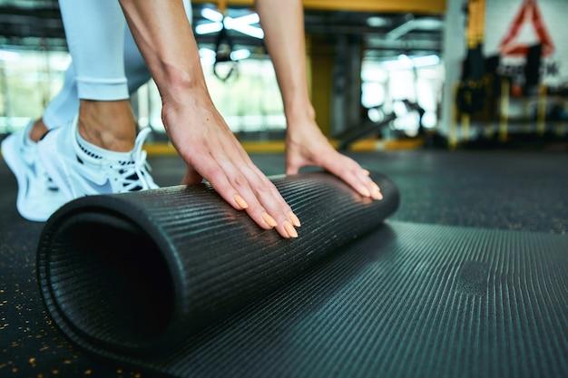 Обрезанный снимок фитнес-женщины в спортивной одежде, катящейся по коврику для йоги во время тренировки в тренажерном зале. спорт, хорошее самочувствие и здоровый образ жизни