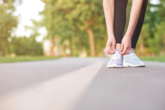 Copyspace 스포츠 운동 활동 활력 레크리에이션 운동 스포츠 개념을 실행하기 전에 신발 끈을 묶는 피트 니스 여자의 자른 샷.